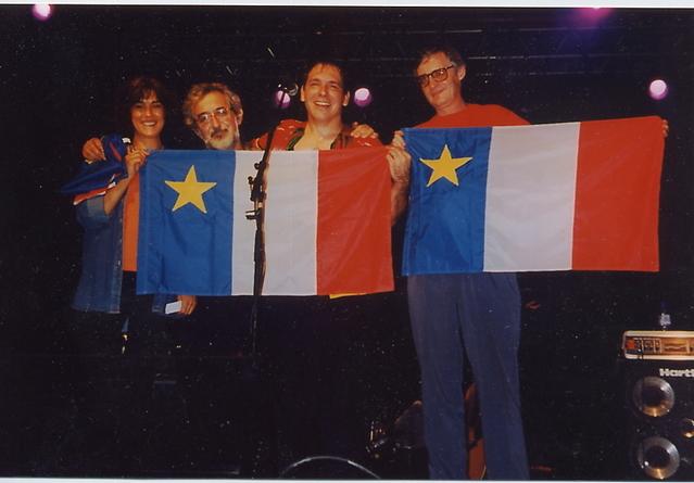 Patrice Boulliane remet le drapeau acadien à Annie Benoit, Maurice Segall et Albert Weber